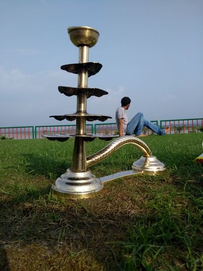 Chirag Brass Diya Diya - Oil Lamp Teenager Boy Foreground Focus Sitting Random EyeEmNewHere EyeEm Gallery EyeEm Selects EyeEm Eyeemphotography Temple Eyeem Market EyeEm Team Spirituality Sky Grass Summer In The City My Best Travel Photo