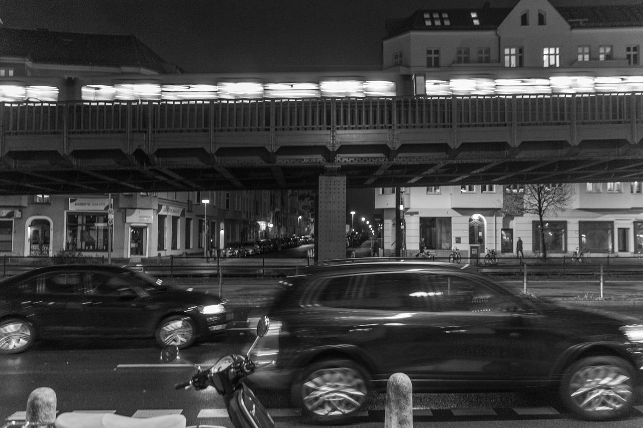 transportation, car, architecture, built structure, mode of transportation, motor vehicle, land vehicle, building exterior, city, motion, night, illuminated, street, blurred motion, road, building, on the move, outdoors, parking, bridge, architectural column, parking garage, garage