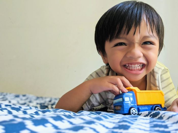 Portrait of cute boy with toy on bed