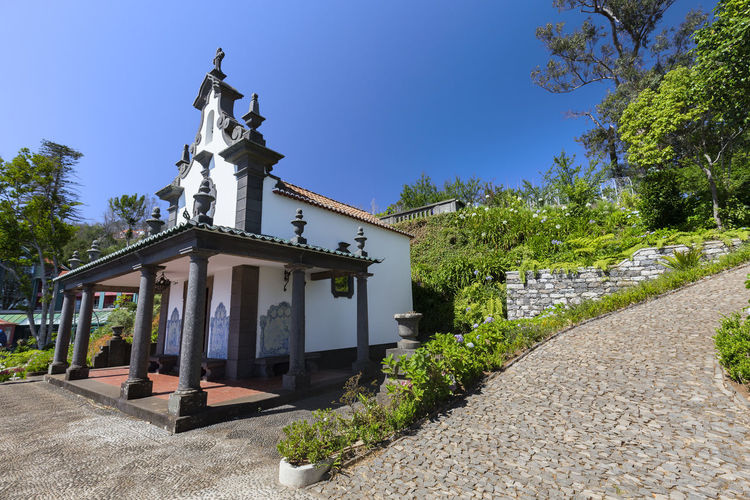 The Sancta Maria Chapel surrounded by intricate cobblestone pathways near the Jardim Tropical Monte Palace in Funchal. Architecture Botanical Gardens Church Funchal Jardim Tropical Monte Palace Madeira Madeira Island Portugal Portuguese Terrace Tourist Travel Trip Cobblestone Destination Explore Flower Iglesia Island Jardim Quinta Sancta Maria Chapel Summer Tourism Traditional