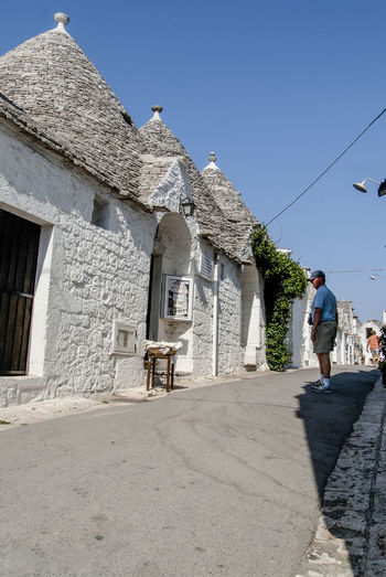The magic of Alberobello's Trulli travel location - It was really amazing to know this particulars constructions full of charming and to ear the history about the Alberobello's Trulli in the Italy Apulia region (Puglia). The history said that the Alberobello's origins date back to the Middle Age. The settlers built the houses with stone and without cement and with the easiest way to demolish them in the case of an inspection by the Kingdom of Naples, thus avoiding paying taxes. Another interesting thing is the decorative pinnacles and symbols painted on many roofs of the trulli that were often used to identify the different religions of their inhabitants. Albelobelo Italia Viajes  2019 EyeEm Awards The Traveler - 2019 EyeEm Awards The Architect - 2019 EyeEm Awards The Photojournalist - 2019 EyeEm Awards The Street Photographer - 2019 EyeEm Awards Italy EyeEm Gallery EyeEm Best Shots Eyeem4photography Architecture Built Structure Building Exterior Sky Real People Building Full Length Sunlight Lifestyles One Person Day Nature Clear Sky Walking Leisure Activity Casual Clothing Rear View Adult Men Outdoors