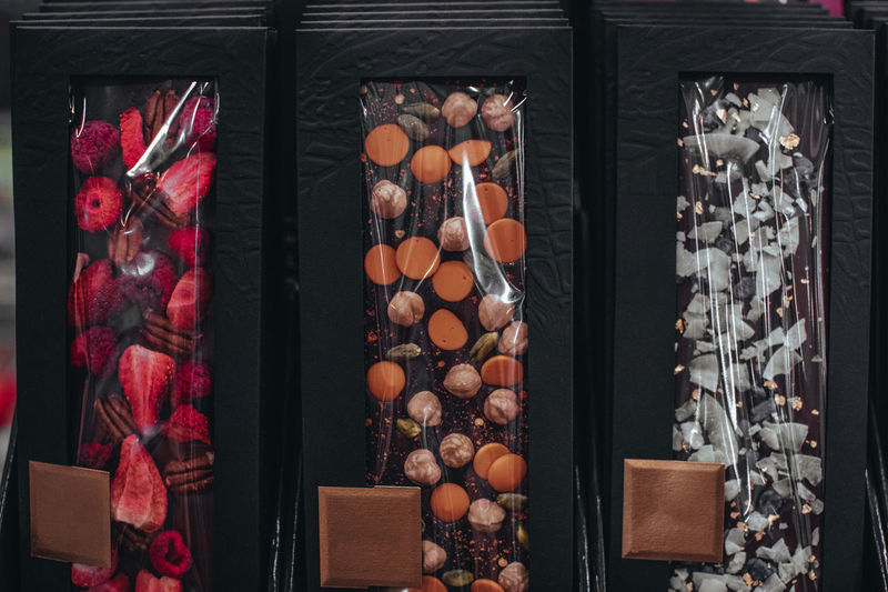 Handmade chocolate bars with dried cranberries, raspberries and pistachios, strawberries, nuts.