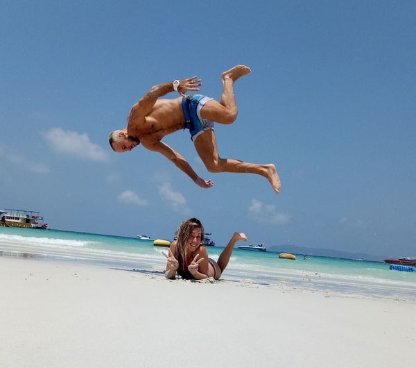Full length of man jumping over woman at beach during sunny day