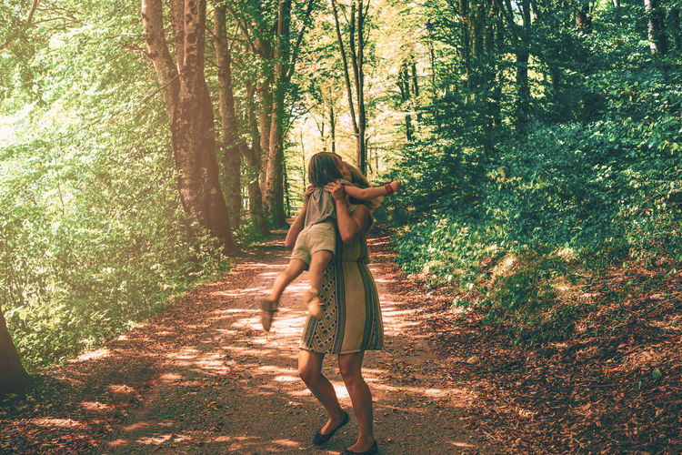 Woman carrying daughter while walking amidst trees in forest