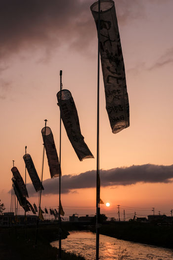 Low angle view of silhouette flags against sky during sunset