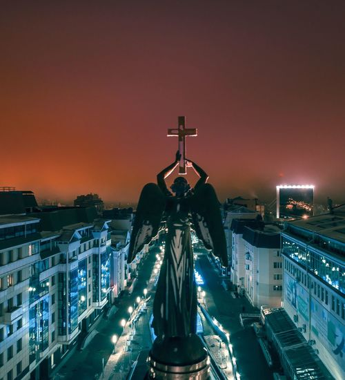 Angel Statue With Cross Against Sky In City At Night
