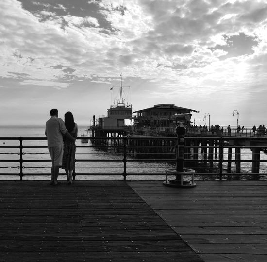 Rear View Of Couple Standing On Bridge Over Sea Against Sky