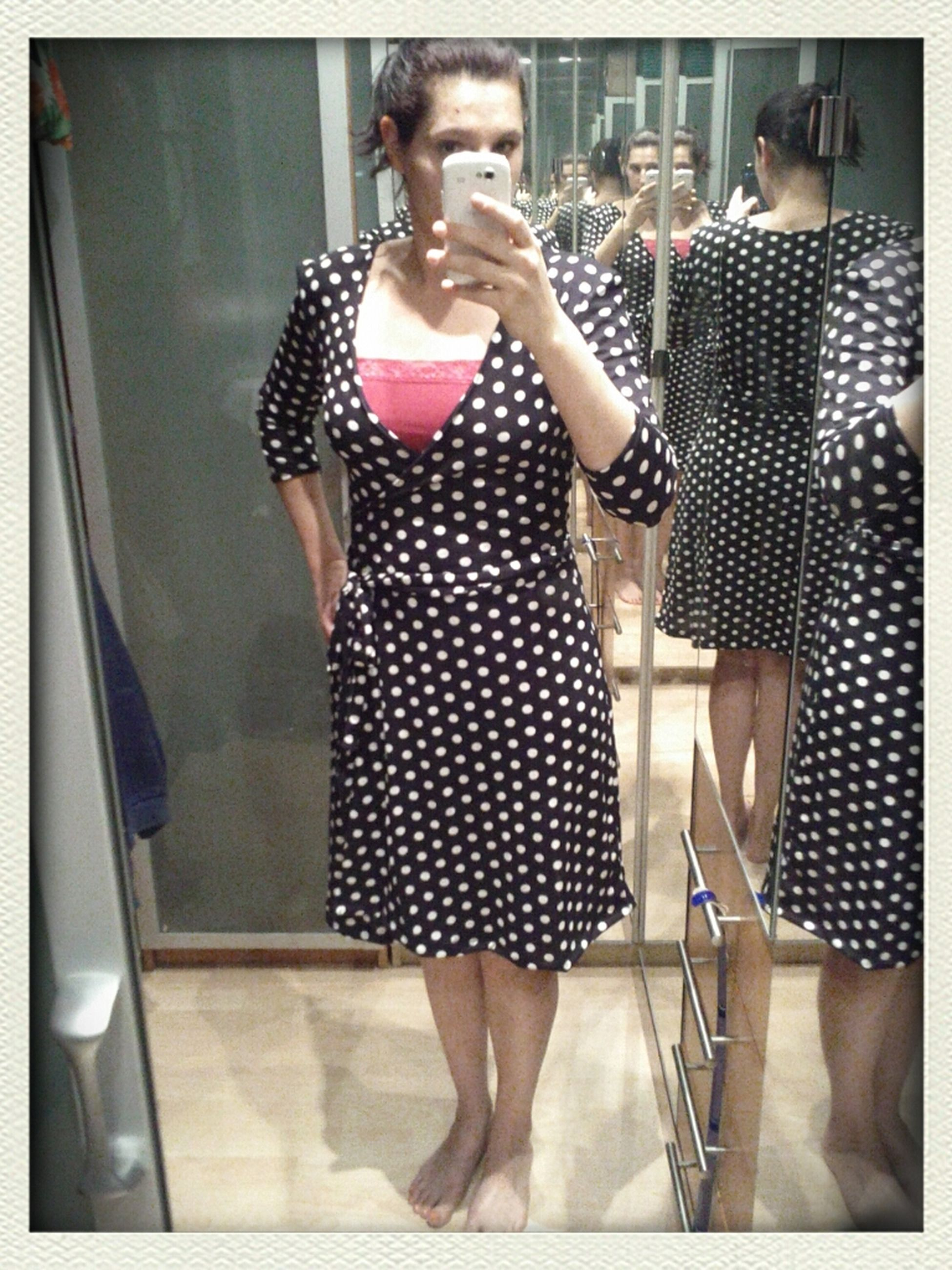 indoors, lifestyles, young adult, leisure activity, casual clothing, standing, transfer print, wireless technology, young women, person, front view, technology, smart phone, full length, three quarter length, holding, mirror, communication