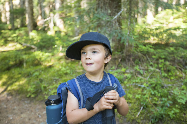 Portrait of boy standing in forest