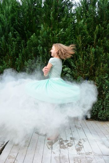 Side view of happy girl spinning with smoke against plants at park