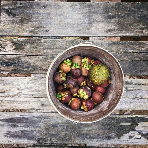 Mangosteen with wooden background Fruit Local Fruit Mangosteen Food And Drink Food Healthy Eating Freshness Wellbeing Directly Above Fruit Still Life No People High Angle View Day Outdoors Close-up Table Wood - Material Ready-to-eat Bowl Vegetable Container Textured