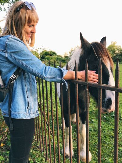 Side view of woman touching horse at ranch