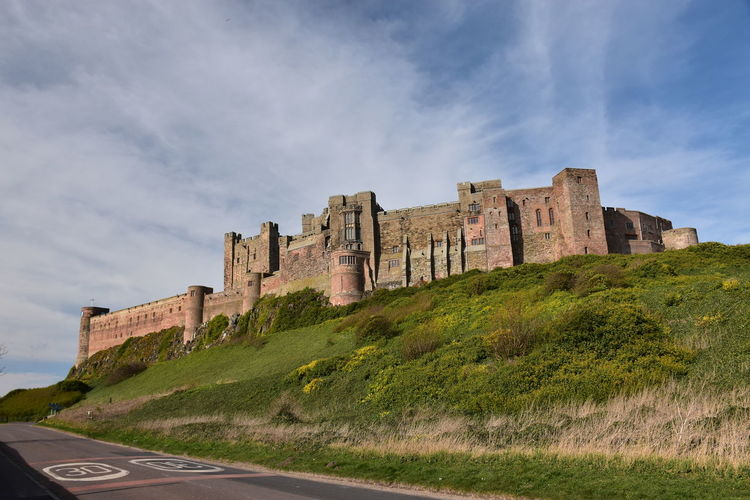 Architecture The Past History Built Structure Sky Building Exterior Low Angle View Cloud - Sky Nature Ancient Travel Destinations No People Day Travel Outdoors Ancient Civilization Ruined Blue Sky Castle Bamburgh Bamburgh Castle Lookingup Grass Green Hill Hillside Hilltop Historic Historical Building Fortification Fortified Wall Tourism Tourist Attraction  Tourist Destination Northumberland Rock - Object Rock Formation Impressive Architecture Building Imposing