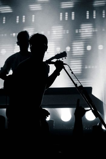 Silhouette singer and guitarist performing during music concert