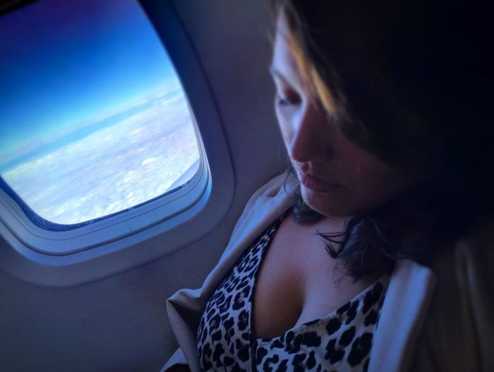 Pretty woman naps on a plane. Somewhere over Jackson, MS. Plane Nap Woman window seat Airplane The Traveler - 2018 EyeEm Awards