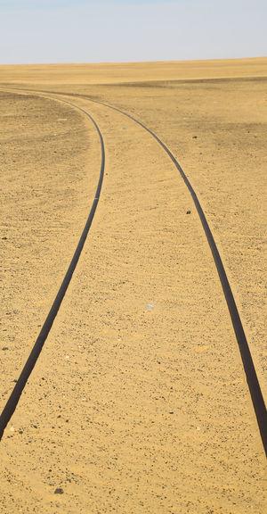 Tire tracks on desert land against clear sky