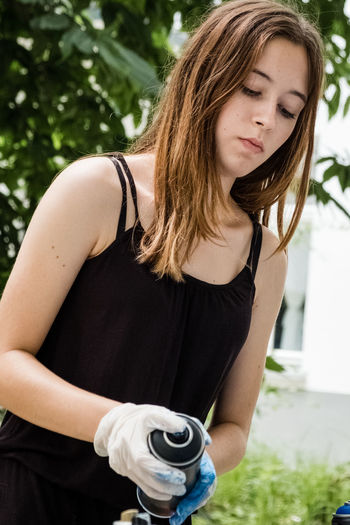 Young woman holding spray can while standing in back yard