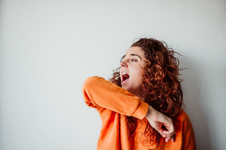 Mid adult woman coughing while standing against wall