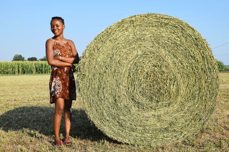 Full Length Of Smiling Woman Standing By Hay Bale On Field