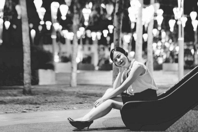 Portrait of smiling woman sitting on slide at park