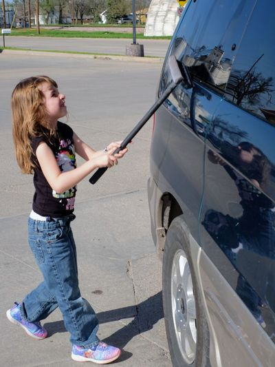 Full length of girl cleaning car window on road