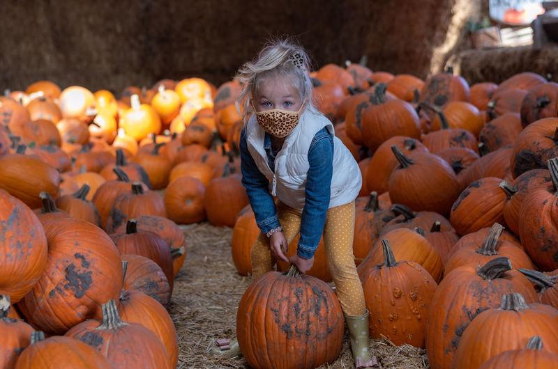 Portrait of smiling girl wearing mask holding pumpkin in farm