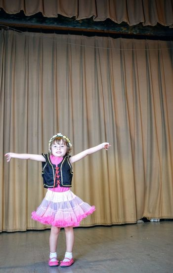Happy girl performing against stage curtain