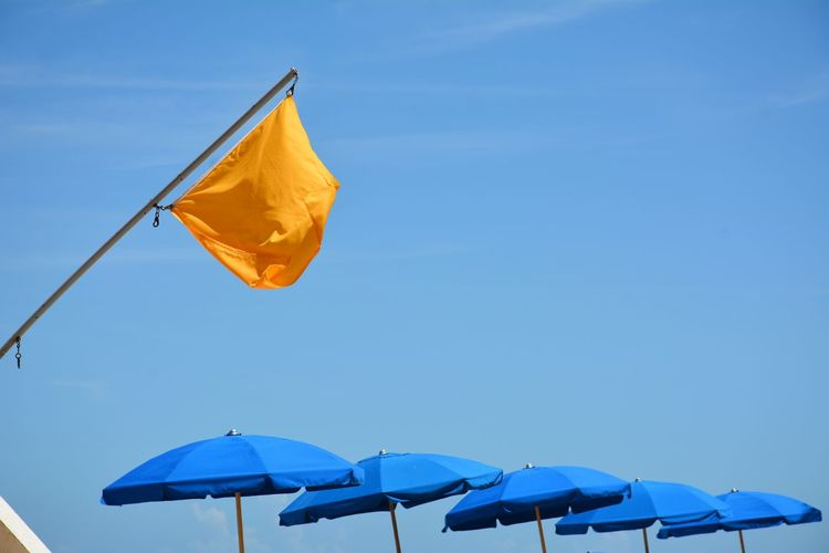 Flag and umbrellas at the seashore against blue sky