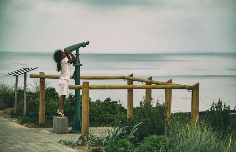 Side view of person on railing by sea against sky