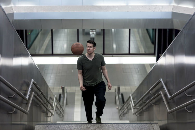 Handsome adult holding a basketball walking up the stairs. Adult Athletic Basketball Long Shot Man Public Transportation Sportsman Stairs Steps Underground Ball Casual Clothing Caucasian Ethnicity Handsome High Angle Model Posing For The Camera Sports Sporty Stairwell Sweatpants T-shirt Urban Walking Walking Up