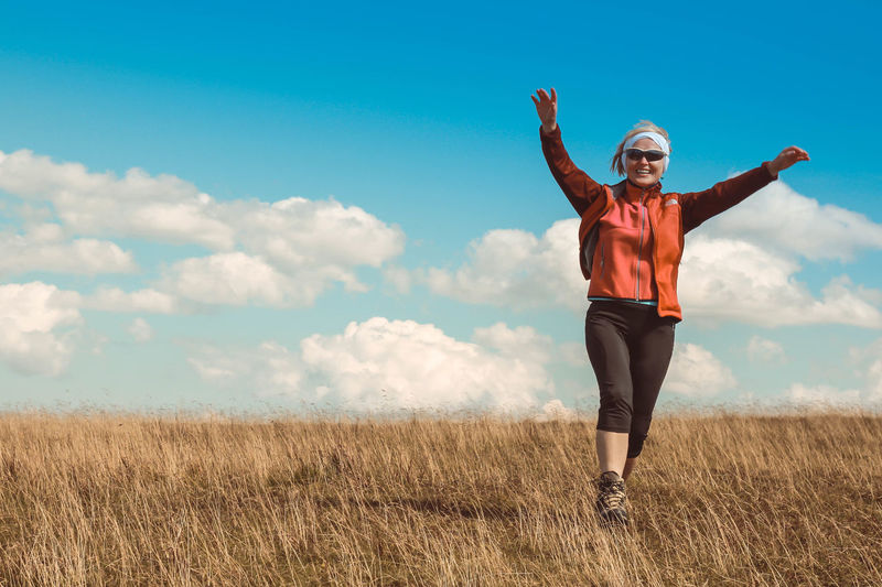 Arms Outstretched Arms Raised Beautiful Woman Beauty In Nature Cloud - Sky Day Field Full Length Grass Happiness Leisure Activity Lifestyles Looking At Camera Nature One Person Outdoors People Portrait Real People Sky Smiling Standing Young Adult Young Women