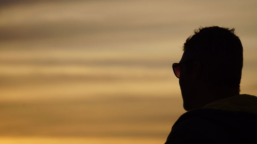 Silhouette man wearing sunglasses against sky during sunset
