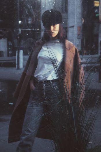 Young woman wearing coat reflecting on window in city
