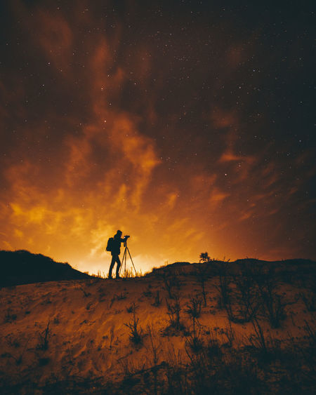 Silhouette man on land against sky during sunset