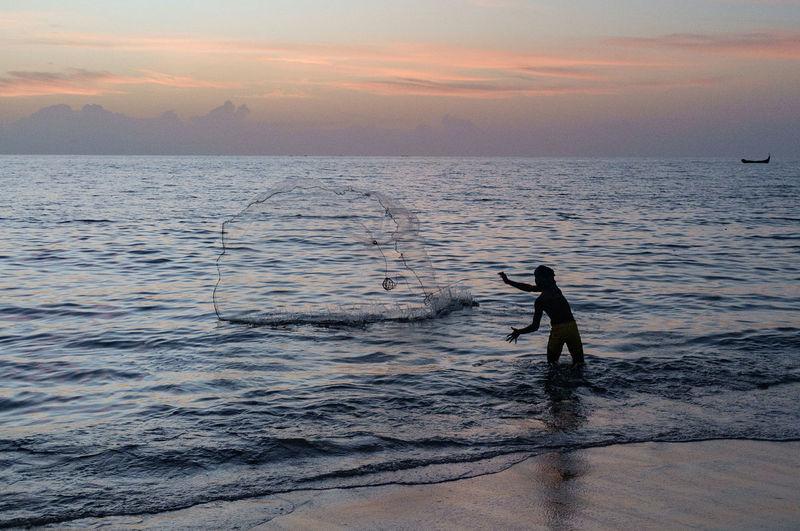 Silhouette Fisherman Fishing On Shore During Sunset