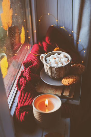 cozy autumn morning at home. Hot cocoa with marshmallows and candle on window in rainy cold day. Spending holidays at home. Temptation Indoors  Candle Food And Drink No People Flame Window Close-up Burning Food Nature Still Life Illuminated Cocoa Marshmallows Autumn Fall Candle Cozy Rainy Days Sweater Mood Home
