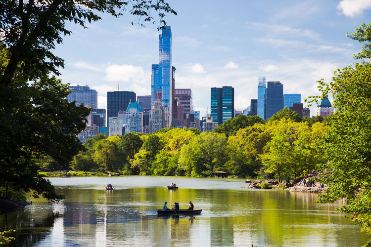Scenic View Of Lake And Trees Against Sky In City On Sunny Day At Central Park
