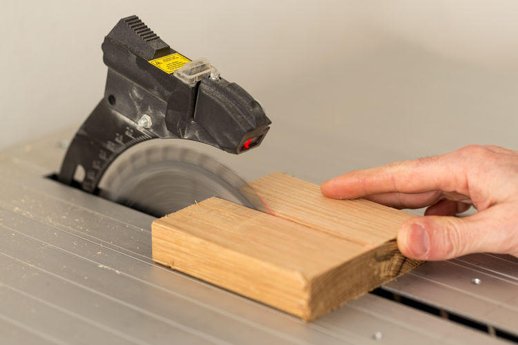 Cropped hand holding plank on table saw at workshop