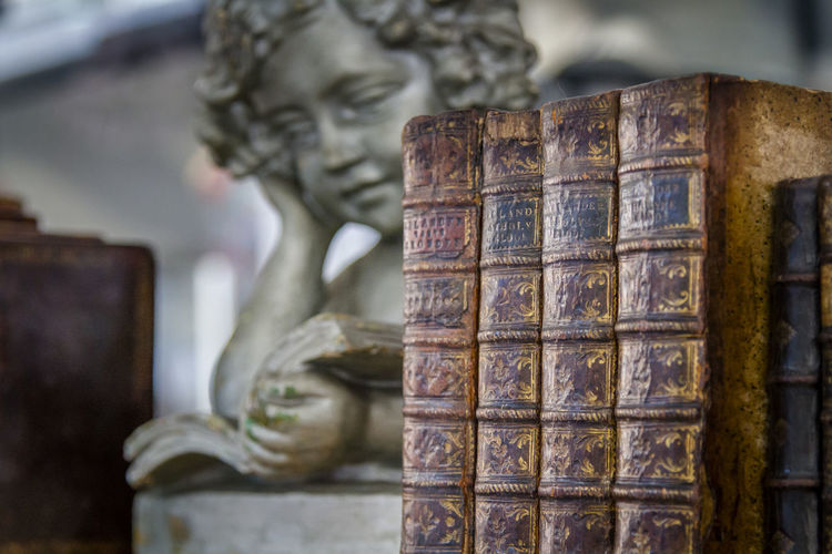 Statue of angel leaning and reading next to old brown books on a bookshelf Books Knowledge Is Power Learning Printed Read Second Hand Angel Backgrounds Bookmarket Education Educational For Sale Hardcover Book Knowledge Literature Liturature Market Stall Novel Old Paperback Publication Second Hand Books Statue Used Vintage