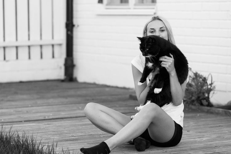 Black Cat Architecture Blackandwhite Photography Cat Love Cuddling With My Kitty Day Domestic Front View Full Length Girl And Cat Hairstyle Holding Cat Leisure Activity Lifestyles Looking At Camera One Person Pets Portrait Real People Resting Time Sitting Tuxedo Cat Women Young Adult Young Women The Portraitist - 2018 EyeEm Awards 50 Ways Of Seeing: Gratitude Human Connection