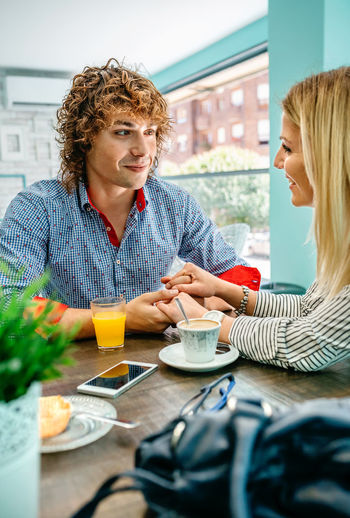 Couple holding hands while sitting at cafe