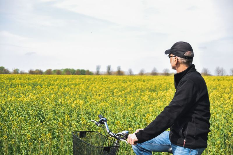 Side view of man standing with bicycle by land against sky
