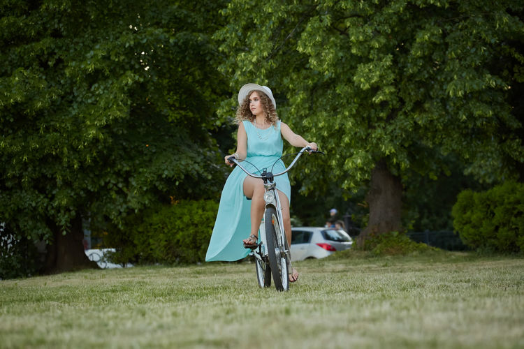 Full length of woman riding bicycle at park