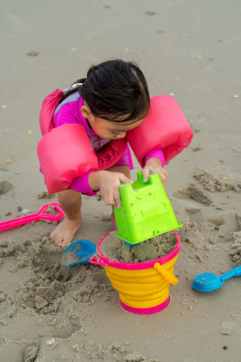 High angle view of girl playing with toy on beach