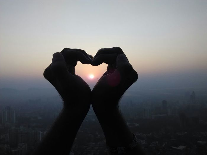 Cropped hands making heart shape with sun in between