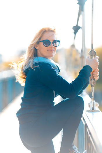 Portrait of woman wearing sunglasses while standing on bridge
