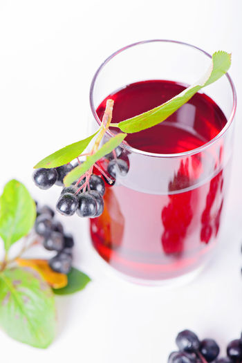 Glass of aronia juice with berries in the light background Aronia Aronia Berries Aroniaberries Close-up Day Drink Food Food And Drink Freshness Fruit Healthy Eating Indoors  Mint Leaf - Culinary Mint Tea No People Red Refreshment Studio Shot White Background