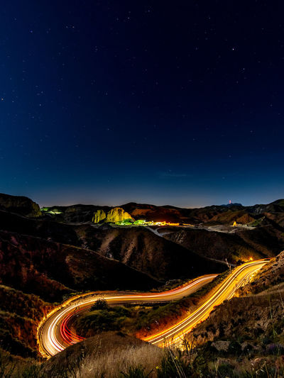 Aerial view of light trails on mountain road against sky at night