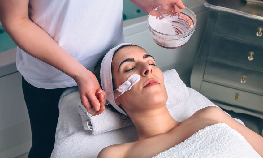Beautician applying facial pack on customer face at spa