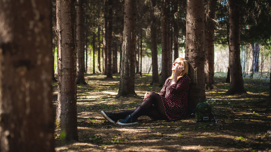 Woman talking on mobile phone while sitting by tree trunk in forest